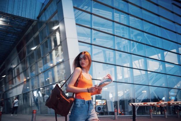 Młoda piękna dziewczyna z plecakiem za ramionami, stojąca na ulicy w pobliżu lotniska.