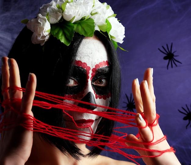 Młoda piękna dziewczyna z tradycyjną meksykańską maską śmierci