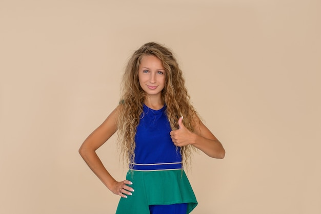 Młoda piękna dziewczyna z uśmiechem na twarzy pokazuje gest kciuka. beżowy kolor tła