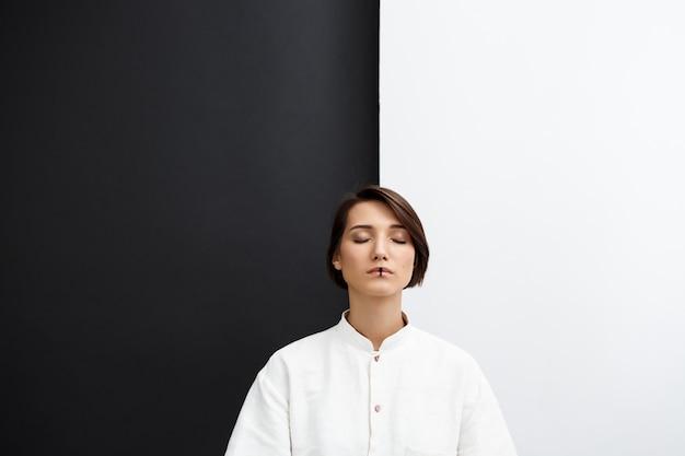 Młoda piękna dziewczyna z zamkniętymi oczami nad czarny i biały ścianą