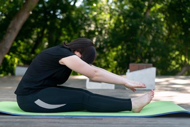 Młoda piękna, elastyczna dziewczyna pochyla się do przodu rękami z pozycji siedzącej