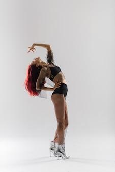 Młoda piękna elastyczna kobieta w czarnym kombinezonie i wysokich obcasach pozuje w studio tańca.