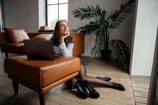 Młoda piękna elegancka biznesowa kobieta zdejmuje buty i pracuje w domu z laptopem