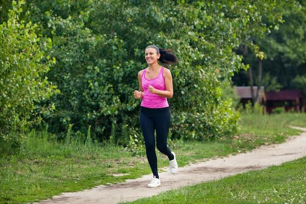 Młoda piękna europejska kobieta z ciemnymi włosami biega na śladzie w parku