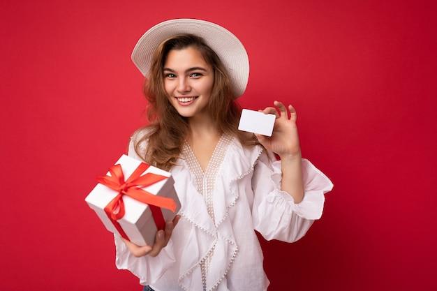 Młoda piękna europejska stylowa brunetka ubrana w białą bluzkę i modny kapelusz na białym tle