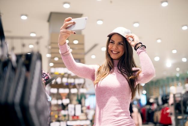 Młoda piękna figlarna dziewczyna przegląda i przymierza kapelusze podczas robienia selfie w sklepie.