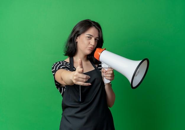 Młoda piękna fryzjerka w fartuch mówi do megafonu, wskazując palcem, patrząc pewnie stojąc na zielonej ścianie