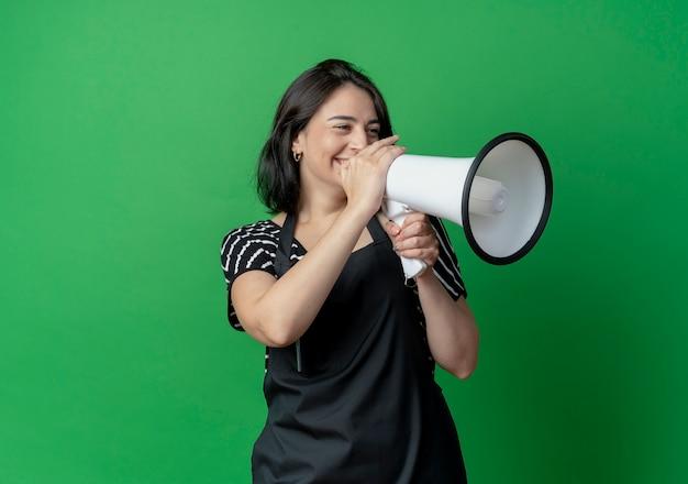 Młoda piękna fryzjerka w fartuch mówi do megafonu z szczęśliwą twarzą stojącą nad zieloną ścianą