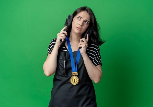 Młoda piękna fryzjerka w fartuchu ze złotym medalem na szyi trzyma dwie szczotki do włosów w pobliżu twarzy, patrząc na bok zdziwiony stojąc nad zieloną ścianą