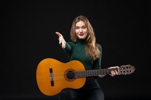 Młoda piękna gitarzystka trzyma swój ulubiony instrument muzyczny witając kogoś w ciemności