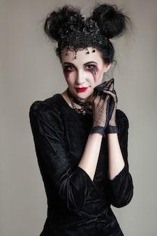 Młoda piękna gotycka kobieta o białej skórze i czerwonych ustach z krwawymi kroplami, ubrana w czarny kołnierzyk