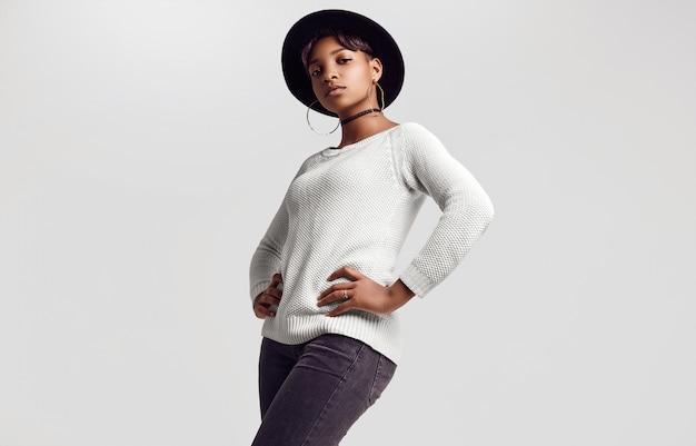 Młoda piękna hipster czarna dziewczyna w biały sweter i kapelusz
