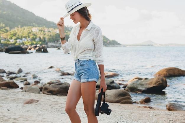 Młoda piękna hipster kobieta na letnie wakacje w azji, relaks na tropikalnej plaży, cyfrowy aparat fotograficzny, swobodny styl boho, morski krajobraz, smukłe opalone ciało, samotna podróż