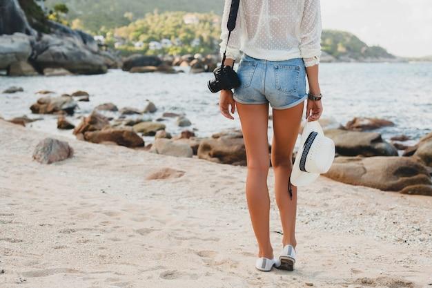 Młoda piękna hipster kobieta na wakacjach, azja, relaks na tropikalnej plaży, cyfrowy aparat fotograficzny, swobodny styl boho, krajobraz morski, smukłe opalone ciało, samotna podróż, akcesoria z bliska