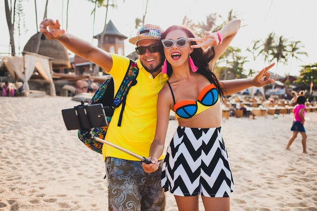 Młoda piękna hipster para zakochana na tropikalnej plaży, robienie zdjęć selfie na smartfonie, okulary przeciwsłoneczne, stylowy strój, letnie wakacje, zabawa, uśmiechnięty, szczęśliwy, kolorowy, pozytywne emocje