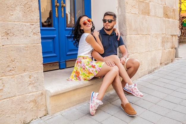 Młoda piękna hipster para zakochanych siedzi na starej ulicy miasta
