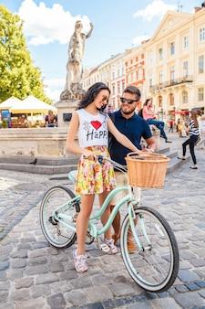 Młoda piękna hipster para zakochanych spacery z rowerem na starej ulicy miasta