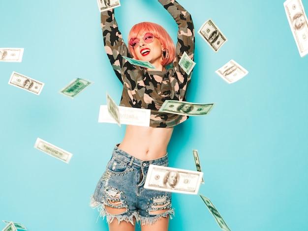 Młoda piękna hipster zła dziewczyna w modne czerwone letnie ubrania i kolczyk w nosie. seksowna beztroska kobieta siedzi w studio w różowej peruce w pobliżu niebieskiej ściany. model wyrzucanie banknotów dolarów pieniędzy