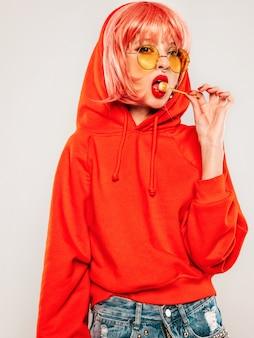 Młoda piękna hipster zła dziewczyna w modnej czerwonej letniej czerwonej bluzie z kapturem i kolczyk w nosie. seksowna beztroska kobieta pozuje w studiu na szarym tle w peruce. gorący model liże cukrowego cukier wokoło