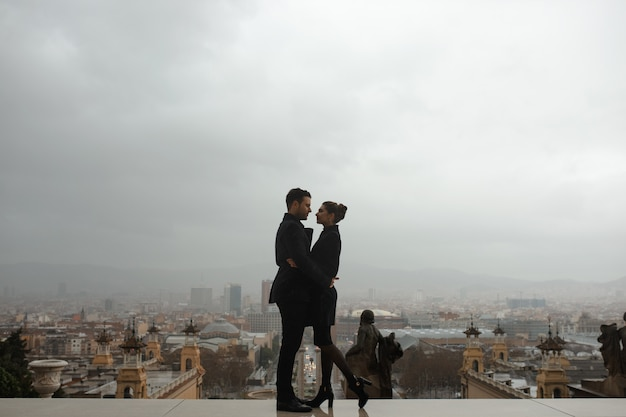 Młoda piękna hiszpańska para zakochanych przytula się w deszczu przed narodowym muzeum sztuki w katalonii. strzał na tle plaza hiszpanii w barcelonie.