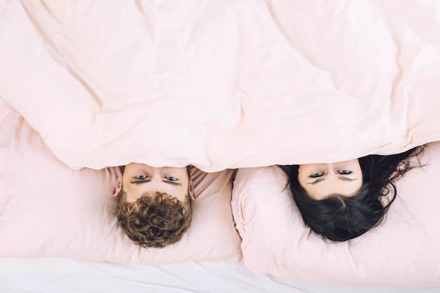 Młoda piękna i szczęśliwa para mężczyzna i kobieta w domu w sypialni w łóżku romantyczny i zakochany