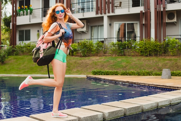 Młoda piękna imbirowa kobieta pozuje przy basenie z plecakiem, zrelaksowany, szczęśliwy, lato, fajny strój hipster, szorty, t-shirt, trampki, okulary przeciwsłoneczne