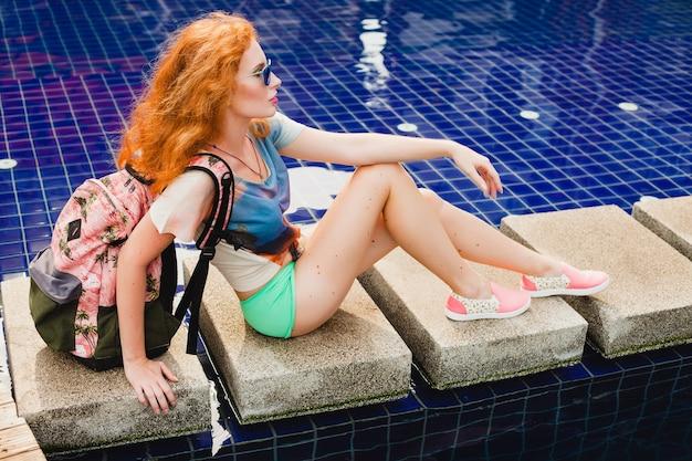 Młoda piękna imbirowa kobieta siedzi przy basenie z plecakiem, zrelaksowany, szczęśliwy, lato, fajny strój hipster, szorty, t-shirt, trampki, okulary przeciwsłoneczne
