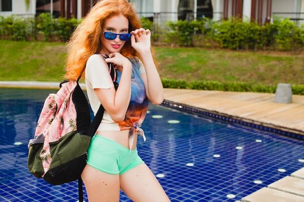 Młoda piękna imbirowa kobieta spaceru w basenie z plecakiem, zrelaksowany, szczęśliwy, lato, fajny strój hipster, szorty, t-shirt, trampki, okulary przeciwsłoneczne