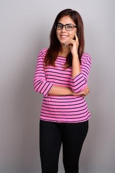 Młoda piękna indiańska kobieta jest ubranym eyeglasses przeciw szarości ścianie