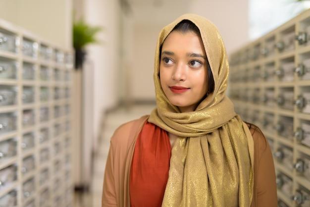 Młoda piękna indiańska muzułmańska kobieta sprawdza poczta