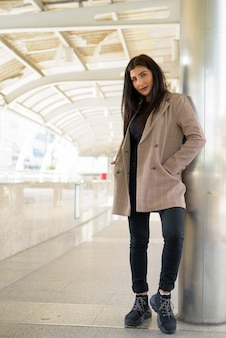 Młoda piękna indyjska bizneswoman na kładce w mieście