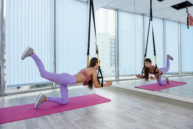 Młoda piękna instruktorka w treningu odzieży sportowej z paskami fitness trx w studio fitness. sport aktywny na rzecz zdrowego stylu życia.