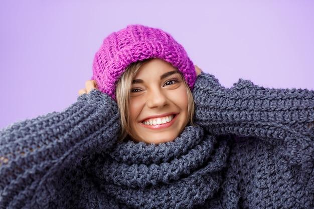 Młoda piękna jasnowłosa kobieta w czapka i sweter z uśmiechem na fioletowo.