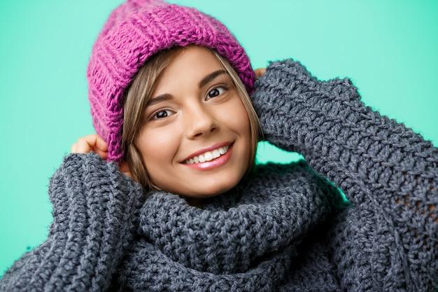 Młoda piękna jasnowłosa kobieta w czapka i sweter z uśmiechem na zielono.