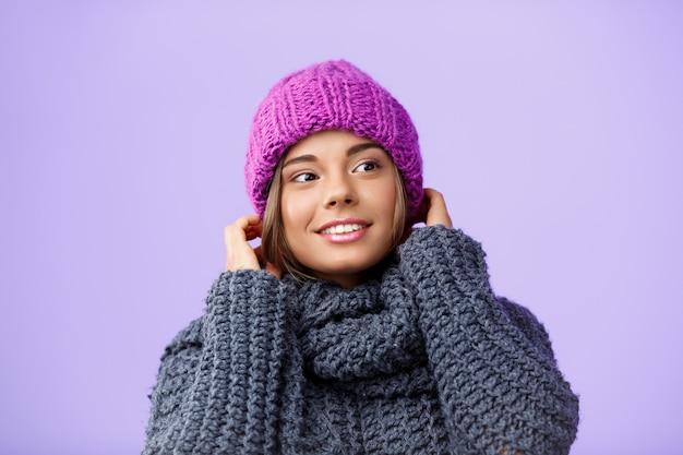 Młoda piękna jasnowłosa kobieta w trykotowym kapeluszu i pulowerze ono uśmiecha się patrzejący stronę na fiołku.