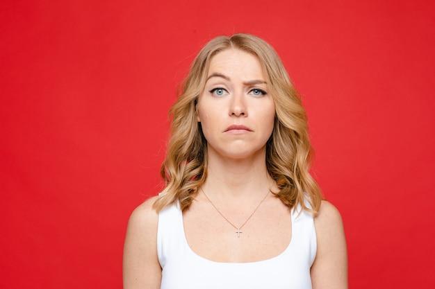 Młoda piękna kaukaska kobieta o średnio jasnych falowanych włosach i nagim makijażu w białej koszulce wygląda z niedowierzaniem, obraz na białym tle na czerwonym tle