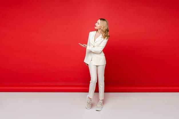 Młoda piękna kaukaska kobieta o średnio jasnych falowanych włosach i nagim makijażu w białym garniturze biurowym pokazuje coś, obraz na białym tle na czerwonym tle