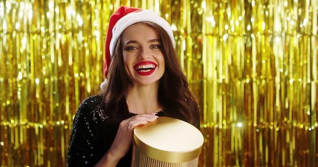 Młoda piękna kaukaska kobieta w święty mikołaj kapeluszu otwiera pudełko