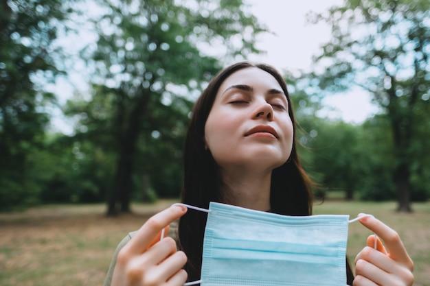 Młoda piękna kaukaska kobieta zdejmuje z twarzy medyczną maskę ochronną na naturze, oddychając czystym, świeżym powietrzem.