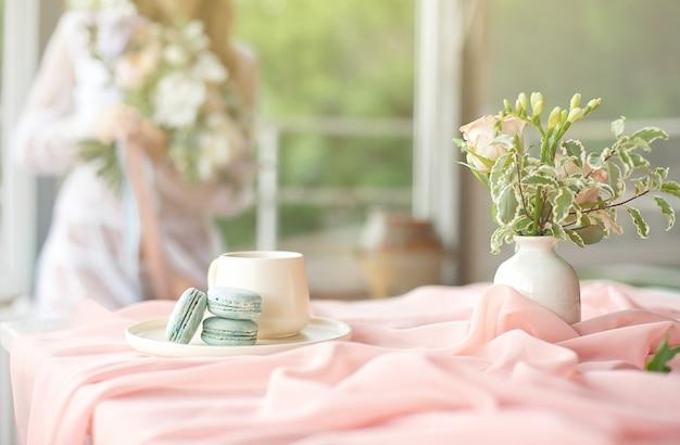 Młoda piękna kaukaska panna młoda cieszy się śniadanie z francuskiego makaronika i kawę na drewnianym stole z szyfonowym różowym obrusem i wazą z kwiatami