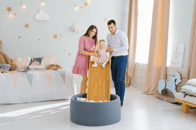 Młoda piękna kaukaska rodzina bawi się ze swoją roczną córką w pokoju dziecięcym. dziewczyna zjeżdża po zjeżdżalni z piłkami do basenu
