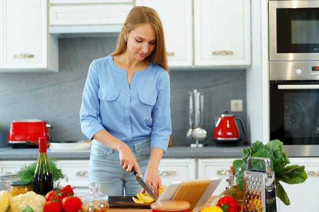 Młoda piękna kaukaski kobieta gotowania i korzystania z jej cyfrowego tabletu w kuchni