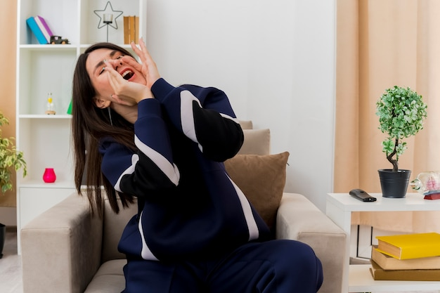Młoda piękna kaukaski kobieta siedzi na fotelu w zaprojektowanym salonie trzymając ręce wokół ust, wzywając głośno kogoś z zamkniętymi oczami