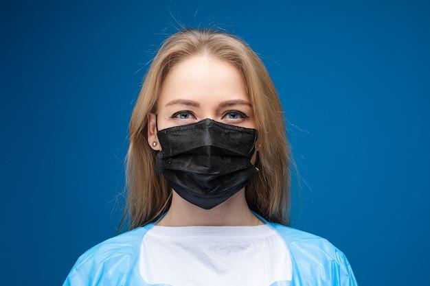 Młoda piękna kaukaski kobieta w niebieskiej sukni medycznej iz białą maską medyczną na twarzy patrzy w kamerę