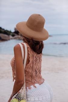 Młoda piękna kaukaski opalona sprawna kobieta w dzianiny i kapelusz na plaży