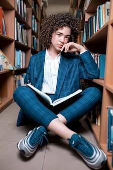 Młoda piękna kędzierzawa dziewczyna w szkłach i błękitnym kostiumu obsiadaniu z książkami w bibliotece.