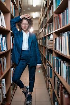 Młoda piękna kędzierzawa dziewczyna w szkłach i błękitnym kostiumu stoi w bibliotece
