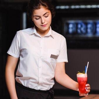 Młoda piękna kelnerka serwująca koktajl. profesjonalny pracownik zapewniający najlepszą obsługę restauracji