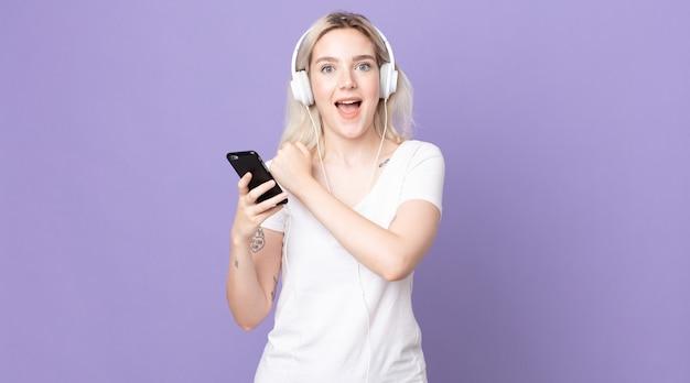 Młoda piękna kobieta albinos czuje się szczęśliwa i staje przed wyzwaniem lub świętuje ze słuchawkami i smartfonem