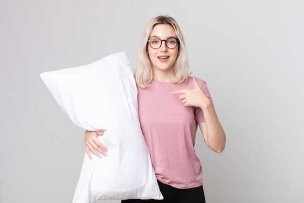 Młoda piękna kobieta albinos czuje się szczęśliwa i wskazuje na siebie z podekscytowaną piżamą i trzymającą poduszkę